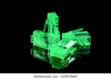 Connector rj-45. Four neon green transparent connectors rj45 for network and internet. Close up macro isolated on black background with reflection.
