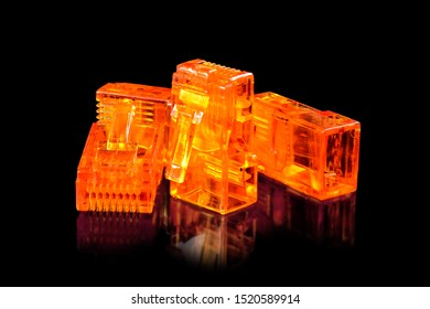 Connector rj-45. Four orange transparent connectors rj45 for network and internet. Close up macro isolated on black background with reflection.