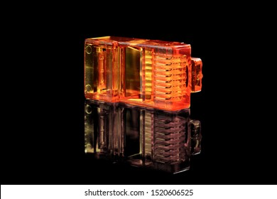 Connector rj-45. Orange transparent connector rj45 for network and internet. Close-up macro isolated on black background with reflection.