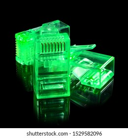 Connector rj-45. Three neon green transparent connectors rj45 for network and internet. Close-up macro isolated on black background with reflection.