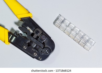 Connectors and tool for crimping of internet cable on white background