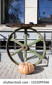 The conposition of the old wheel and ripe pumpkin. This is located in the street in Chisinau. The vertical image.