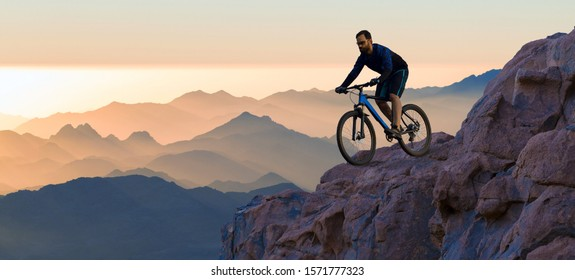 Conquering mountain peaks by cyclist in shorts and jersey on a modern carbon hardtail bike with an air suspension fork . Beautiful view from the mountain. Panoramic view for banner.
