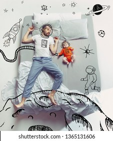 Conquerors of outter space. Top view photo of young man and his child sleeping in a big white bed. Dreams concept. Painted dream about cosmos, flight, stars, planets, moon, Mars, rocket, galaxy.