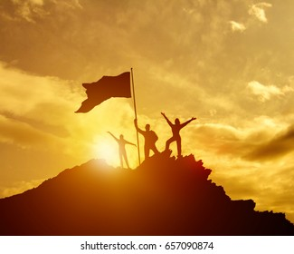 The conquest of the summit, three silhouette families, the father of mother and child, the flag of victory on the top of the mountain, hands up. A man on top of a mountain. Against the evening sky