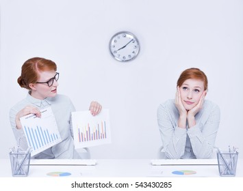 Conscientious and distracted office worker sitting at desk