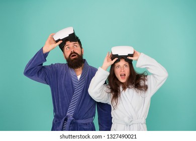 Conscious awakening. Return to reality. Man and woman explore vr. VR technology and future. VR communication. Exciting impressions. Awakening from virtual reality. Couple in bathrobes wear vr glasses.