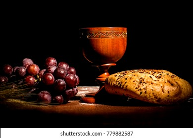 consecration cup with bread and grapes on the table