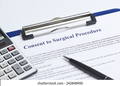 Consent for surgical procedure with calculator on white table.