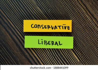 Conservative and Liberal write on sticky notes isolated on Wooden Table.