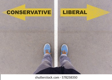 Conservative vs Liberal text on yellow arrows on asphalt ground, feet and shoes on floor, personal perspective footsie concept