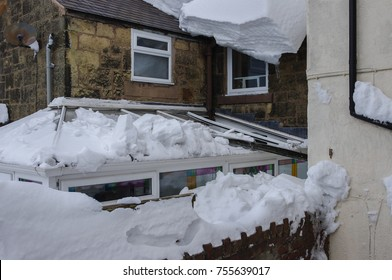 Conservatory damaged by thick heavy snow sliding off a sloping slate roof and crashing through it.