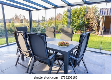 Conservatory of glass with table and chairs in garden