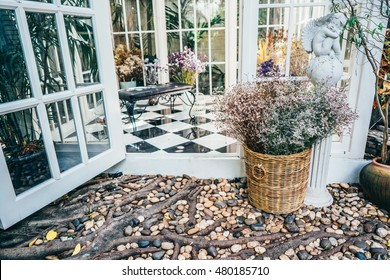 conservatory house chairs plants next to garden with flower bucket