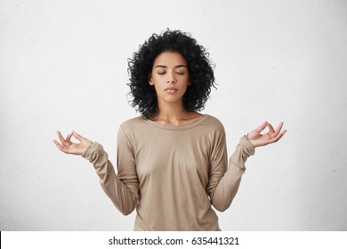 Consideration and praying. Beautiful calm young black female with Afro hairstyle keeping eyes closed while practicing yoga indoors, meditating, holding hands in mudra gesture, thinking about peace