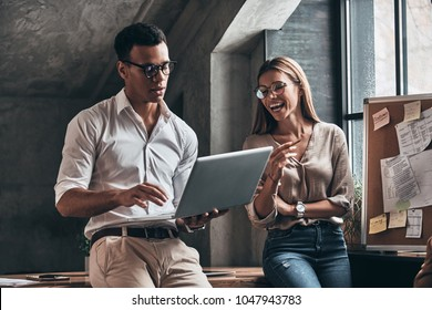Considering new proposal. Two young business people using computer and smiling while working in the office