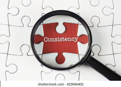 """""""Consistency"""" text on missing puzzle with magnifying glass on it searching for missing puzzle peace"""