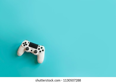 console games and remote control on blue background, play computer games, entertainment, virtual world, flat lay