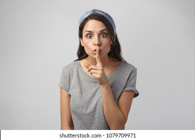 Conspiracy and secrecy concept. Isolated shot of attractive emotional young woman with many secrets keeping eyes popped out and holding finger at her lips, asking not to disclose her secret
