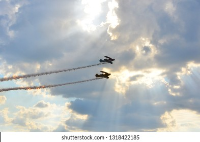 Constanta,Romania - July 14th 2018: Silhouettes of two racing stunt biplanes flying on a cloudy blue sky leaving white smoke trail