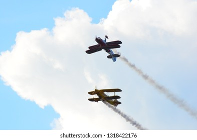 Constanta,Romania - July 14th 2018:Two stunt biplanes performing a calypso pass flying on a cloudy blue sky leaving white smoke trail