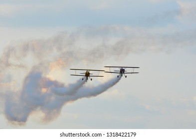 Constanta,Romania - July 14th 2018:Two stunt biplanes flying side by side on a cloudy blue sky leaving white smoke trail
