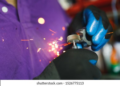 constant-velocity CV joint gear with sparks, polishing with rotary tool