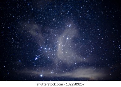 Constellation Orion behind passing clouds shaped like angel wings, stars and star clusters
