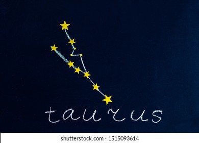 constellation Taurus drawn in chalk and gold stars on a chalkboard looking like a night starry sky