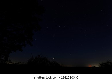 Constellations from left to right Pleiades, Perseus and Cassiopeia with the Hannington Tower lit up in the distance from a field near Oakley Hampshire