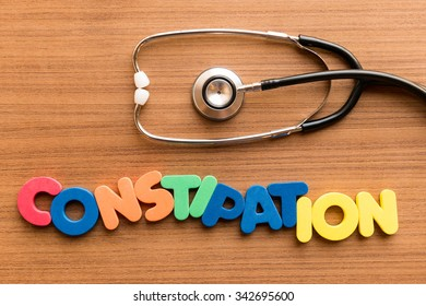 constipation colorful word on the wooden background with stethoscope