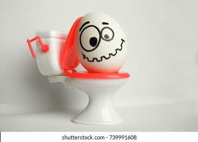 Constipation is a comical concept. an egg with a painted face sitting on the toilet. tuzhitsya. a tense smile. photo for your design.