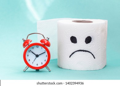 Constipation, indigestion, digestion problem. Alarm clock and toilet paper on light background. creative concept