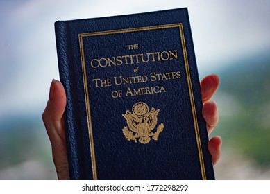 The Constitution of The United States of America book in hand on blurred background.