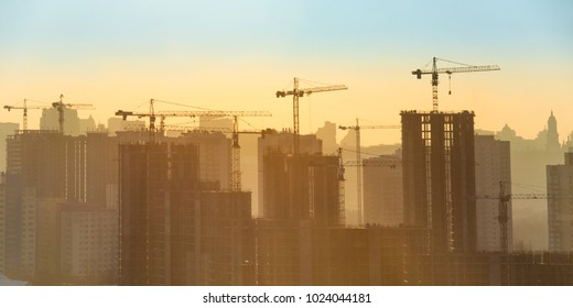 Constraction site with industrial cranes in city at sunset