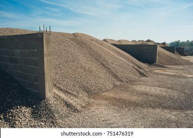 Construction aggregate and gravel dumps at concrete production plant. Side view