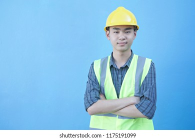 Construction, architecture, building and people concept - smailing a boy in protective helmet at blue background.