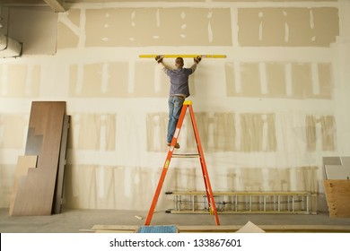 Construction area with man working on ladder