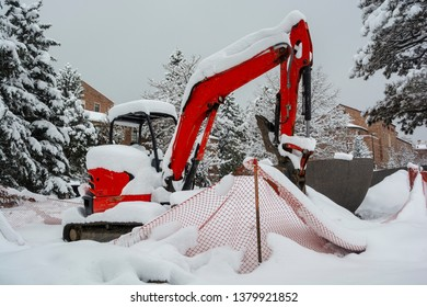 Construction Backhoe Stopped on a Frozen Snow Day