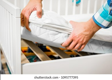 Construction of bed for children. Man arranges a mattress on a cot for a child. Role of the father in child's life. Father folds bed for a newborn child, growing up children, Concept of parenthood.