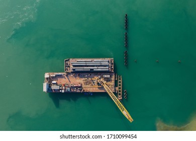 Construction of the berth from a metal sheet pile of the Larsen type, installation of piles of the berth wall with a floating crane . View from above. Aerial photography