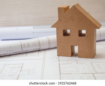 Construction blueprints concept. Housing project drawings and brown carton house model on an office desk. Architect engineer work space