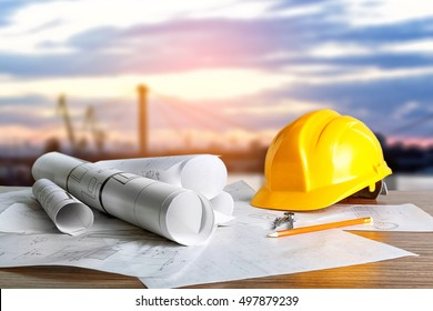 Construction blueprints with tools and helmet on sky background