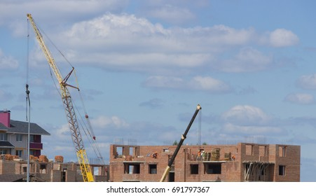 Construction of a brick house with a tower crane.