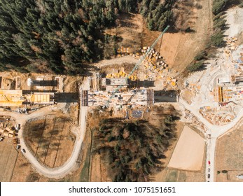Construction of a bridge at the way in mountains. Aerial drone view of site plane.