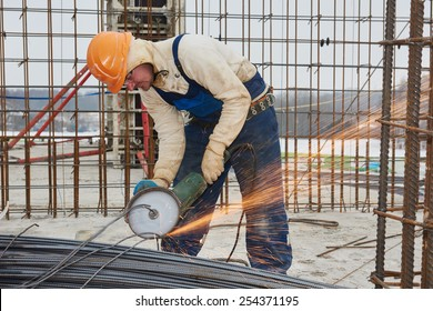 Construction builder worker with grinder machine cutting metal reinforcement rebar rods at building site