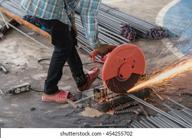 Construction builder worker with grinder machine cutting metal reinforcement rebar rods at building site and unsafe