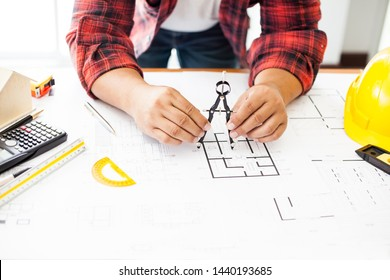 Construction and building concept. Engineers using a Drawing Compass with drawings in construction on blueprints in office.
