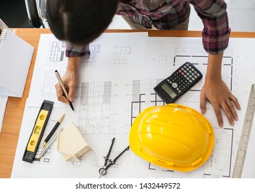 Construction and building concept. Top view of Engineers or architect holding a pen with drawings in construction on blueprints in office.