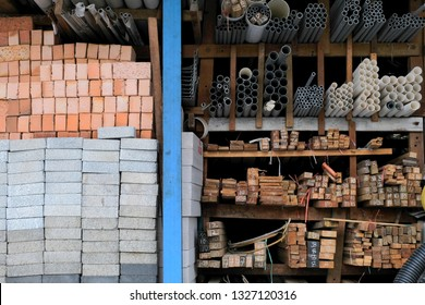 Construction building materials and industrial supplies such as bricks, woods and pipes stacked and arranged for sale at a hardware store front. - Shutterstock ID 1327120316